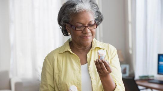 Elderly woman reading the medication bottle.