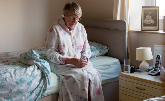 Elderly woman sitting on the edge of the bed.