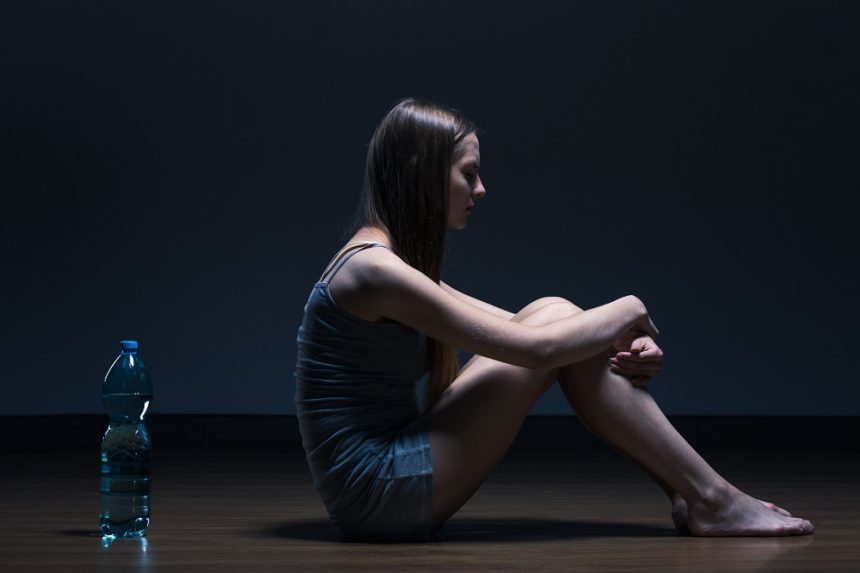 girl sitting with her back to a water bottle