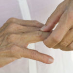 close up of older woman's hands rubbing in pain