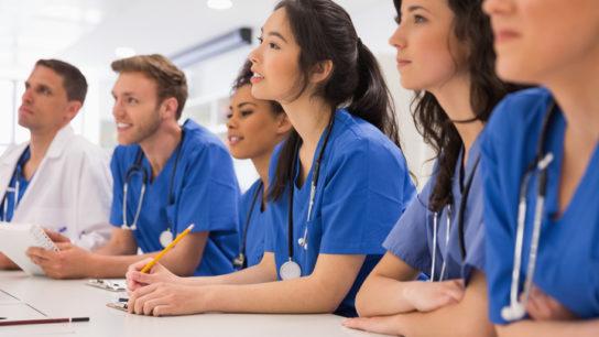 Medical students listening sitting at desk