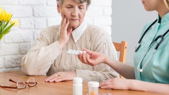 Older woman being handed pills
