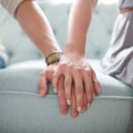 a couple sitting on the couch holding hands
