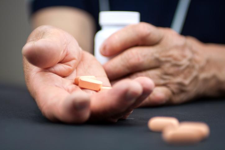 hands with rheumatoid arthritis holding pills