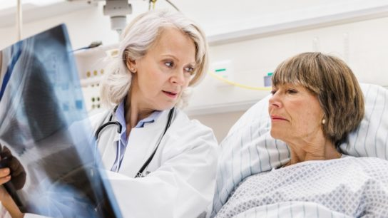 Female patient in hospital bed looking at xray with clincian