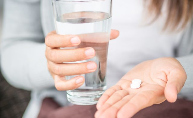 Woman with pill and water