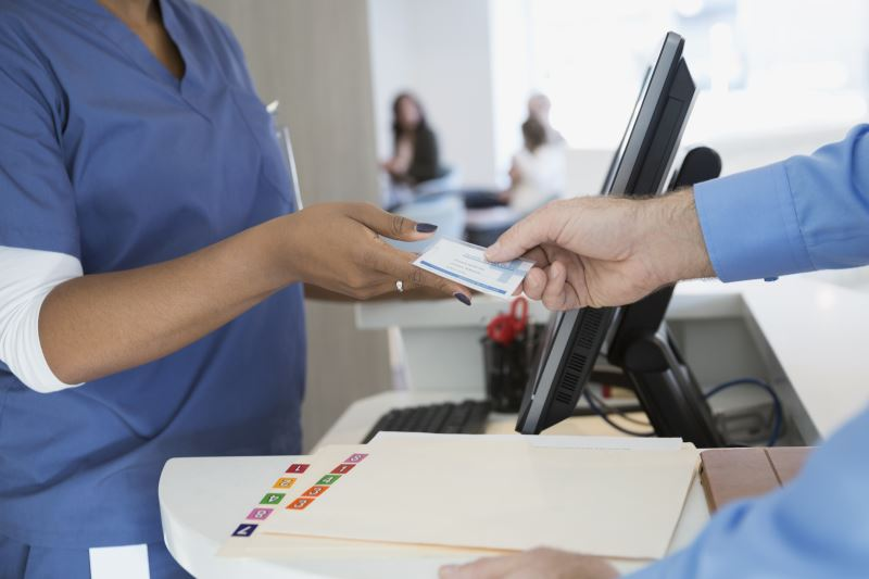 A patient hands over his health insurance card at a clinic.