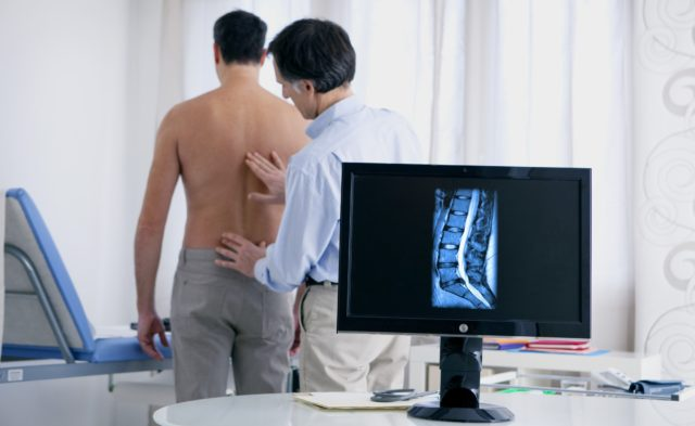 Rheumatologist examining a patient's spine