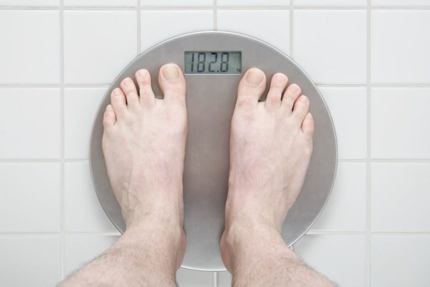 A man weighing himself on a scale