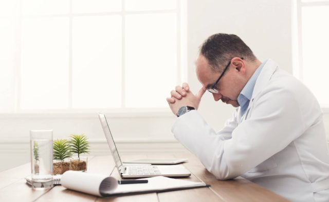 Tired doctor sitting at desk