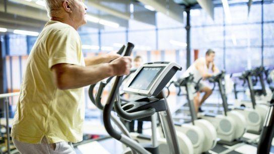 man exercising on elliptical in gym
