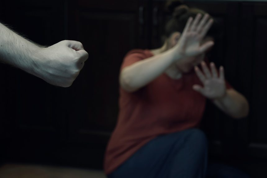 Fist ready to hit a woman in dark room.