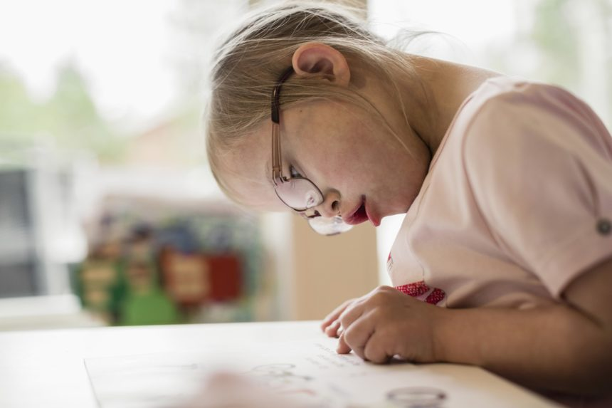 Girl with down syndrome studying at table.