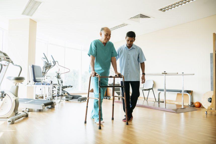 Senior man using walking frame in physiotherapy gym