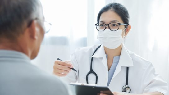doctor wearing face mask meeting with patient