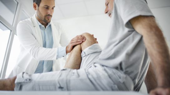 Doctor and patient knee physical therapy