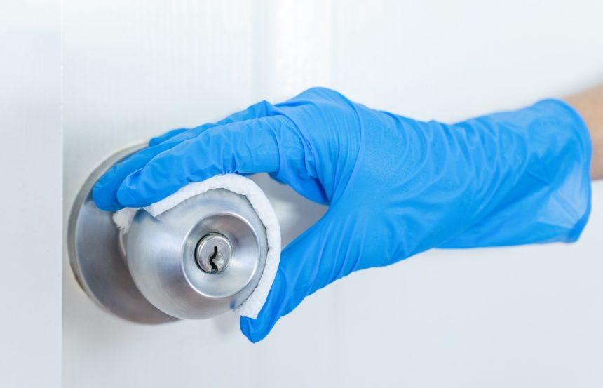 gloved hand cleaning doorknob for covid-19 prevention