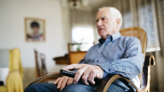 elderly man sitting watching tv