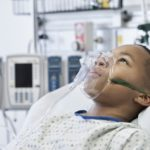 african american child wearing oxygen mask in hospital