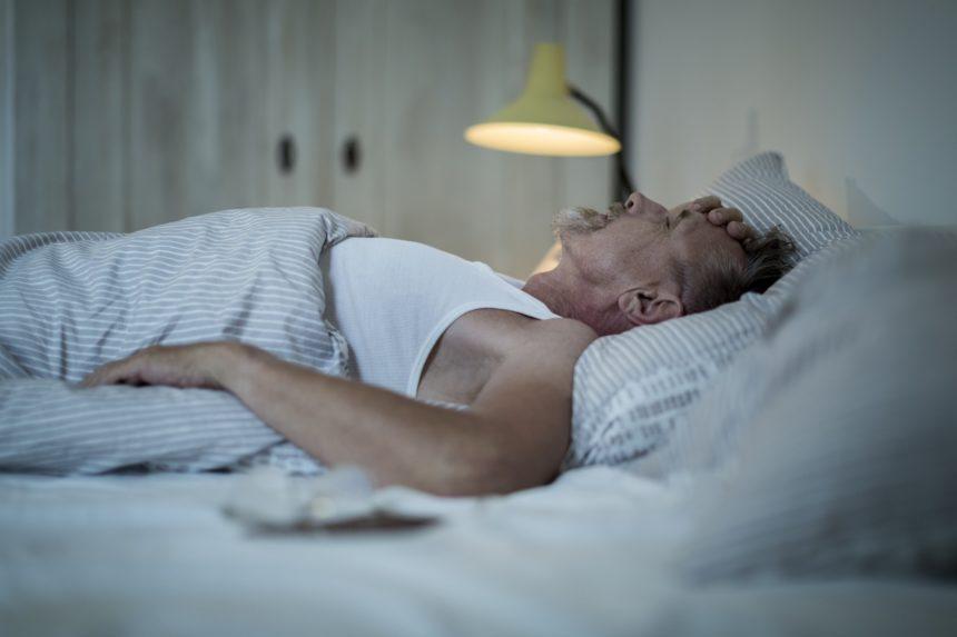 man sleeping, restless in bed