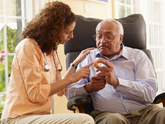 health worker talking to a man about his medication at home