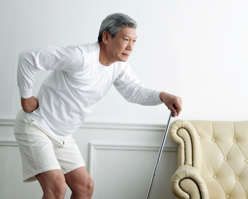 elderly man with hip pain holding cane
