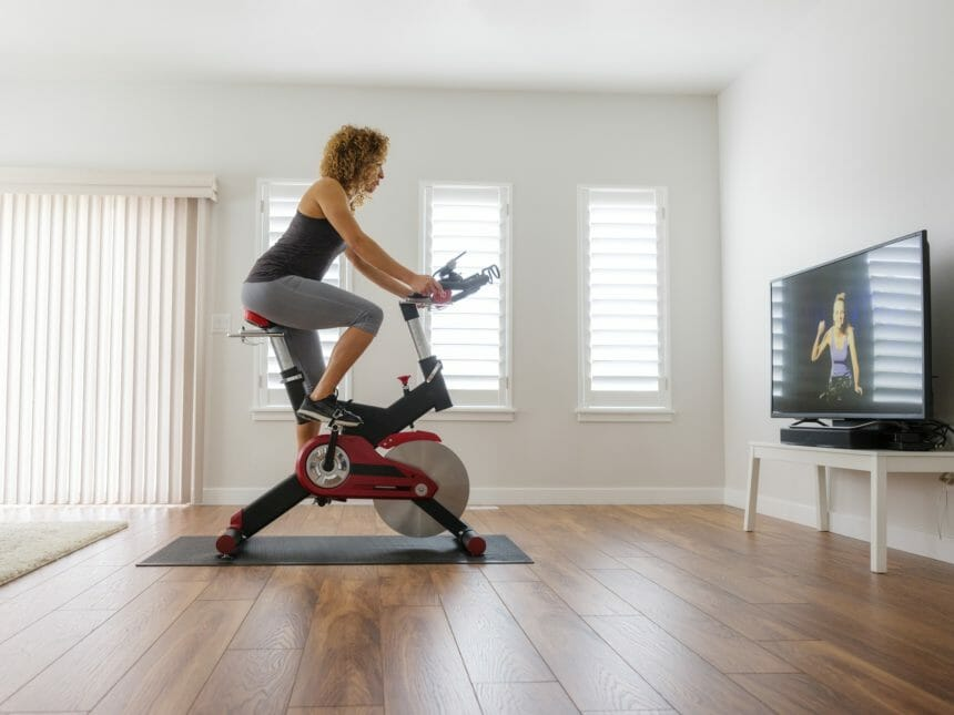 woman exercising at home on spin bike