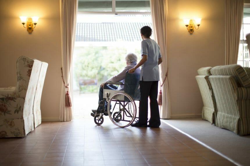 nurse and patient in wheelchair, in nursing home
