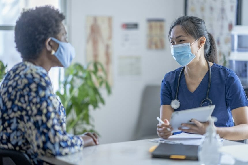 doctor and patient with masks speaking in doctors office