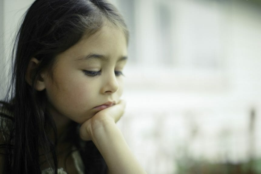 Girl by window with chin resting on hand