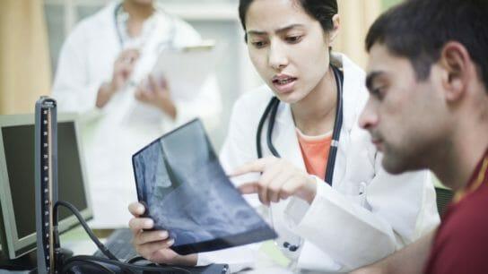 Female orthopedics doctor examining x-ray of patient.