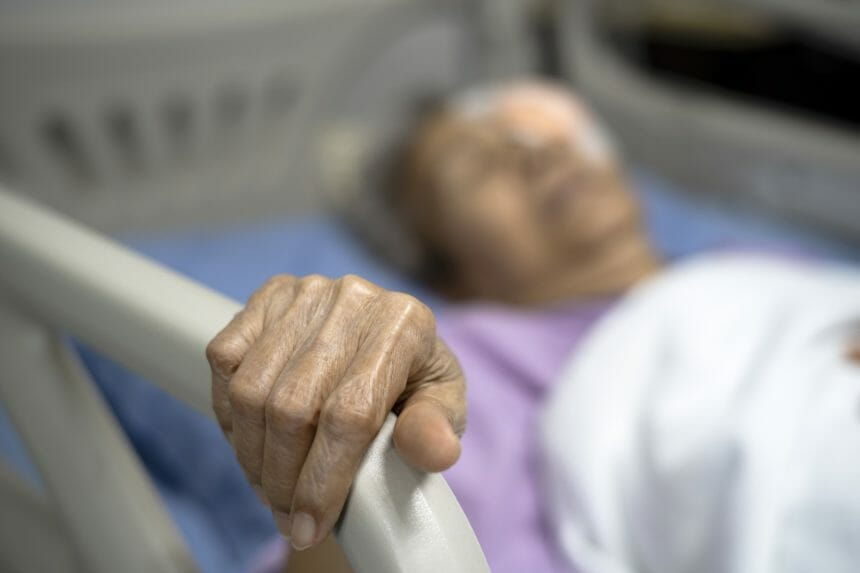 older woman lying in hospital bed