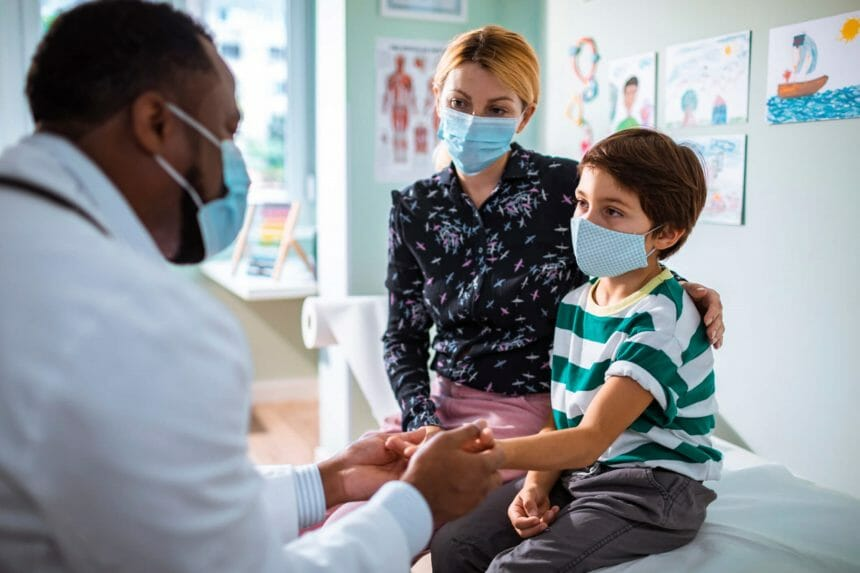 Pediatrician meeting with child patient wearing masks