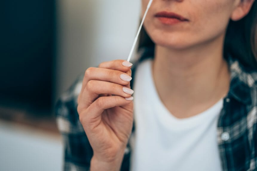 woman self administering COVID-19 nasal test